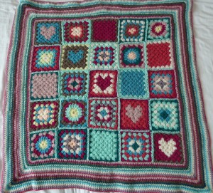 crocheted blanket with hearts and flowers